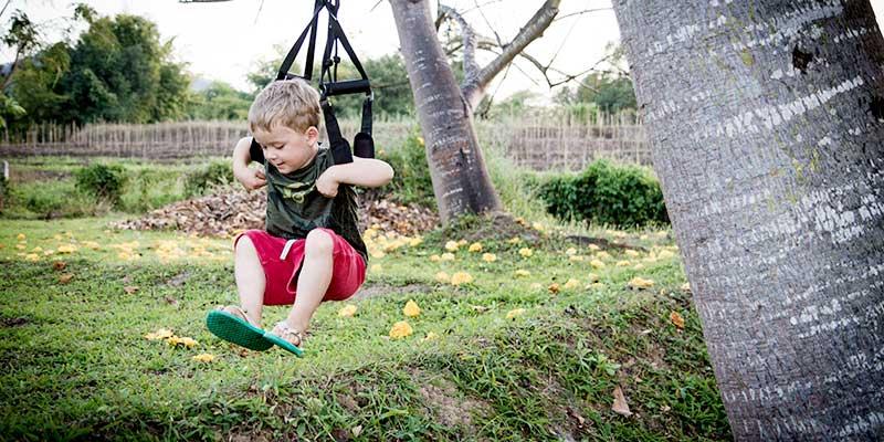 Kind schaukelt am Sling Trainer
